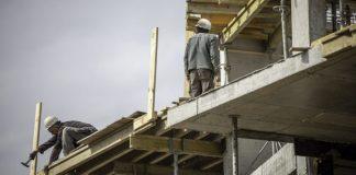 Dos obreros trabajando en la costrucción del esqueleto de hormigón de un edificio.