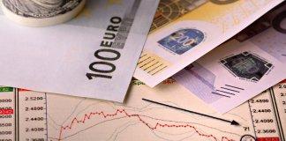 Billetes de cien y doscientos euros sobre una gráfica con una flecha que señala un descenso del valor.