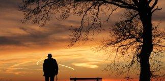 anciano solo ante la puesta de sol