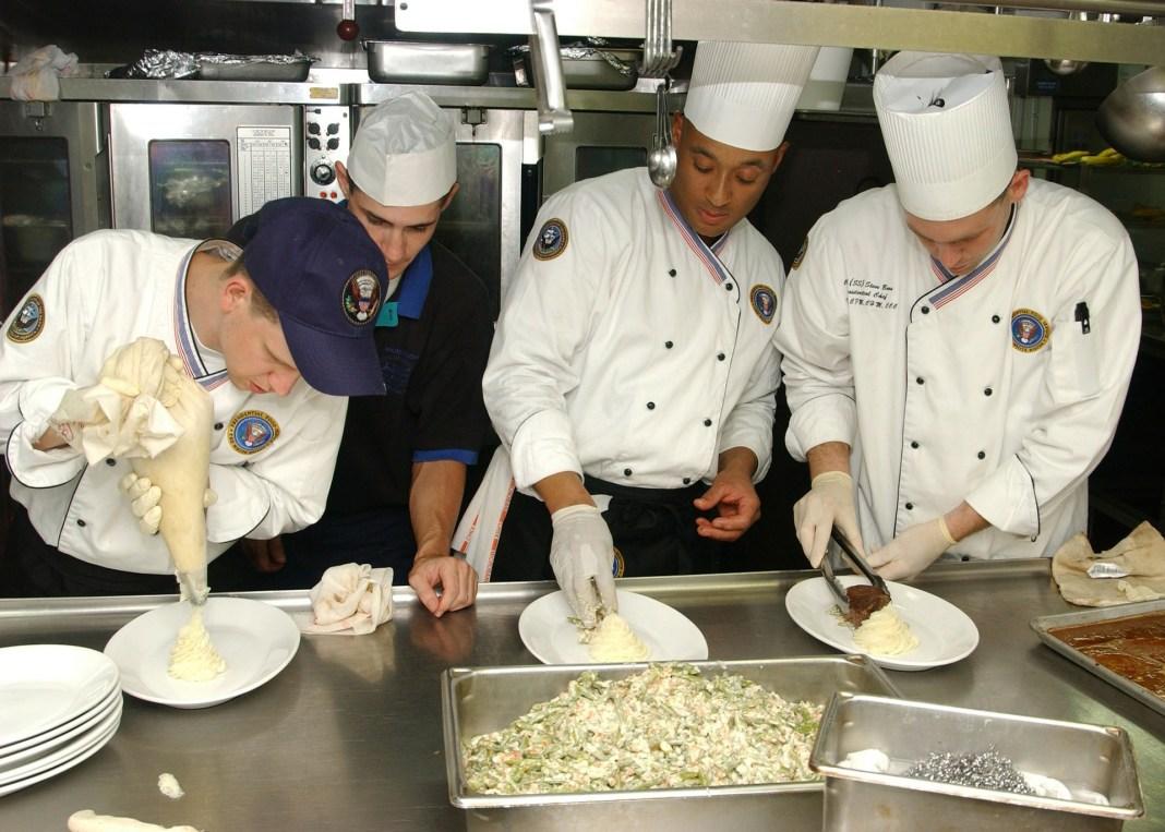 Unos cocineros preparan grandes cantidades de comida.