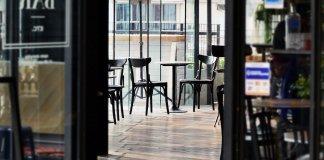 Terraza de un bar con sillas y mesas vacías, vistas desde dentro del local, en la distancia.
