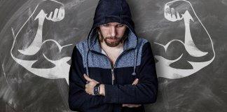 Joven triste, encapuchado, está apoyado en una pizarra donde hay pintados unos brazos que reflejan su fortaleza