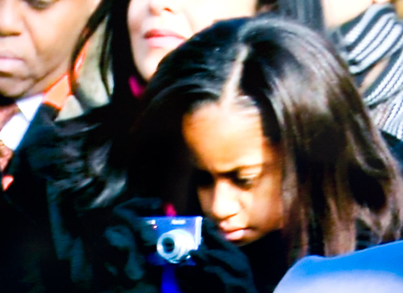 Using her Kodak*, Malia grabs a shot (or maybe video) of her father giving the Inaugural Address today.