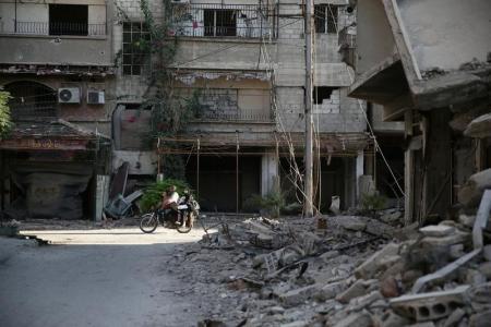 أشخاص يستقلون دراجة بخارية بالقرب من مبنى مدمر في عين ترما في الغوطة شرق دمشق يوم السبت. تصوير: بسام خابيه - رويترز.