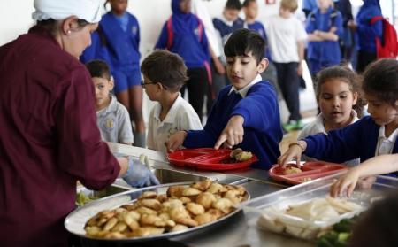 أطفال يتسلمون وجبة في مدرسة في لندن. أرشيف رويترز