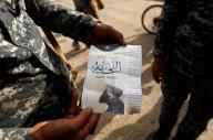جندي عراقي يحمل ملصقا دعائيا عن وجوب اطلاق اللحية في جنوب الموصل يوم 30 اكتوبر تشرين الأول 2016. تصوير: زهرة بنسمرة - رويترز.
