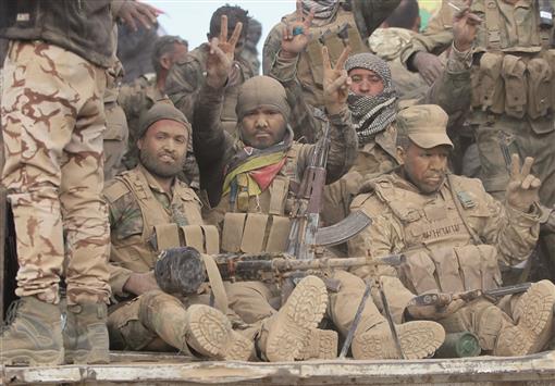 مقاتلون عراقيون خلال توجههم نحو بلدة ام سيجان جنوب الموصل أمس (أ ف ب)