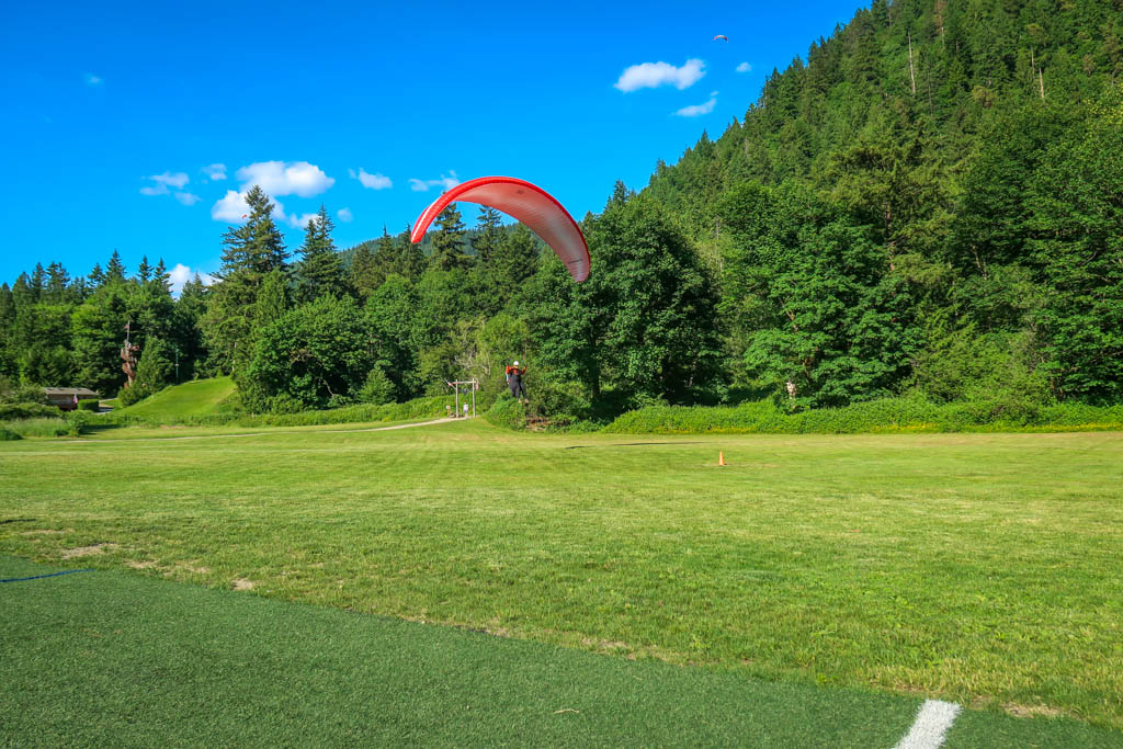 A paraglider lands on the field next to Poo Poo Point Chirico Trail