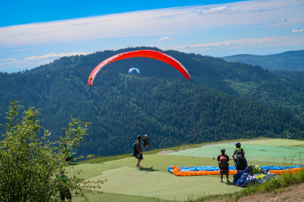 A paraglider launches from Poo Poo Point with another person strapped to him