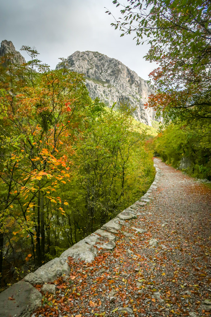 A hiking trail with the tall limestone cliff of Anića kuk looming in the distance