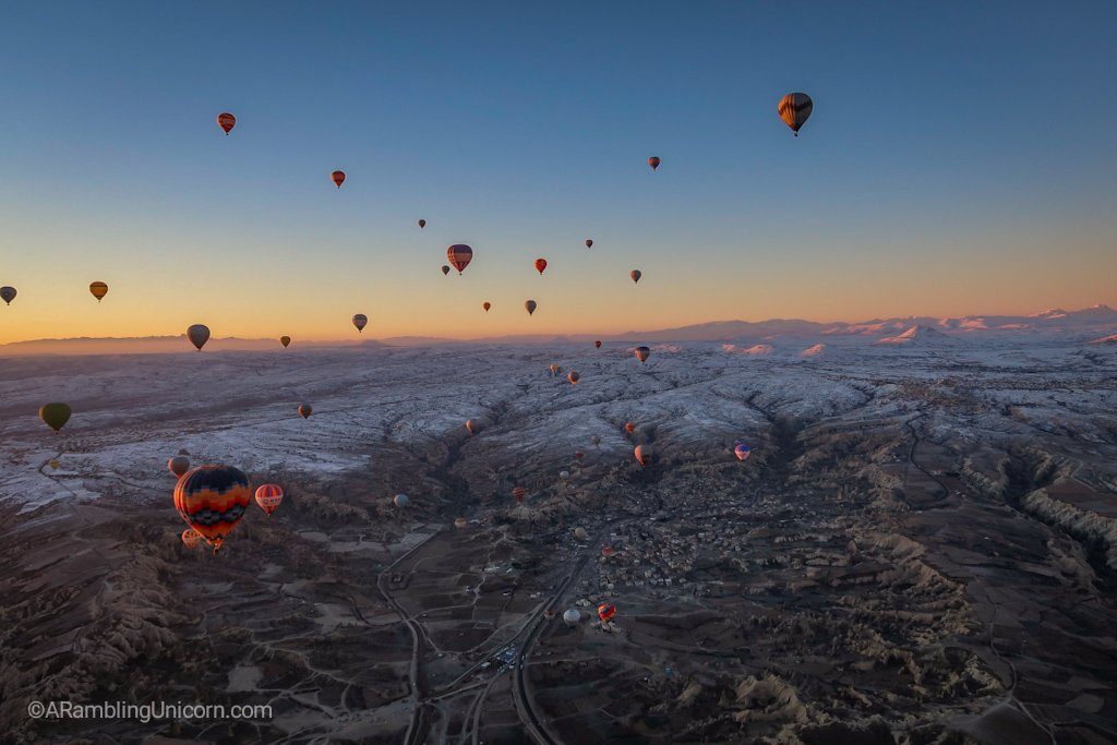 Cappadocia balloon ride with snow covered mountains in the distance.