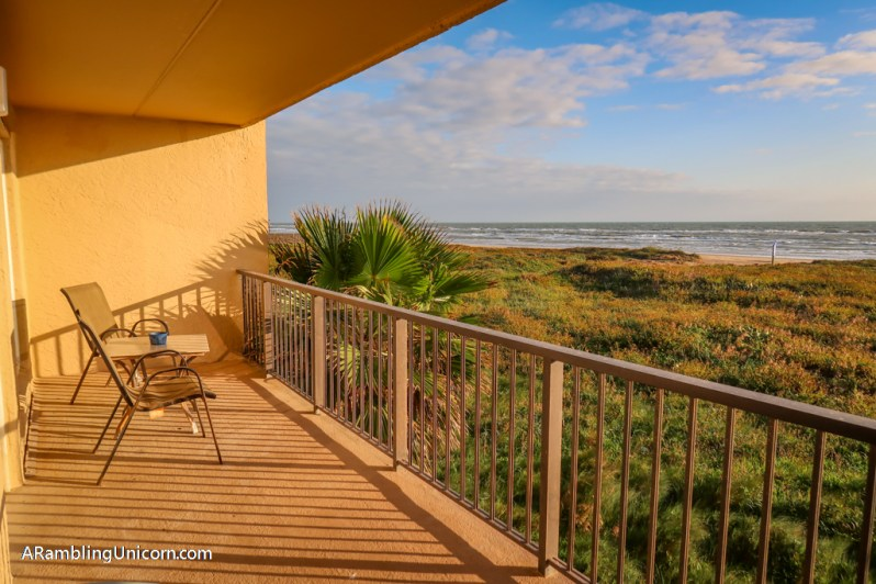 A little table and 2 chairs are set up on the deck facing the ocean, bathed in morning sunlight. A perfect way to spend a South Padre Island vacation.