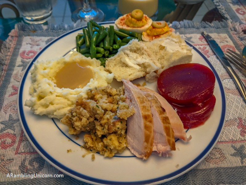 A plate with mashed potatoes & gravy, stuffing, turkey, cranberry sauce, a buttered roll, green beans, and two deviled eggs
