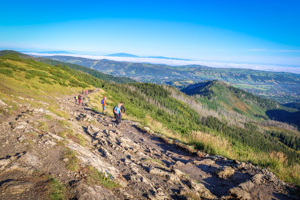 Hikers ascend the Blue Trail along a ridge with sweeping views of Zakopane below