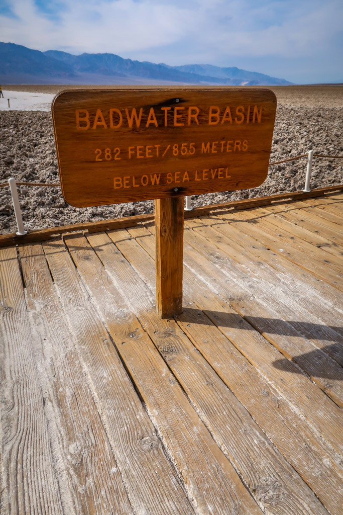 """Sign for Badwater Basin in the middle of the salt flats which reads """"Badwater Basin: 282 feet/85.5 meters below sea level"""""""