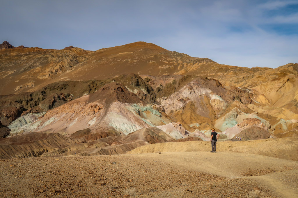 Daniel stands in front of Artists Palette - brown hillside splashed with a range of colors including pink, blue, green and orange.