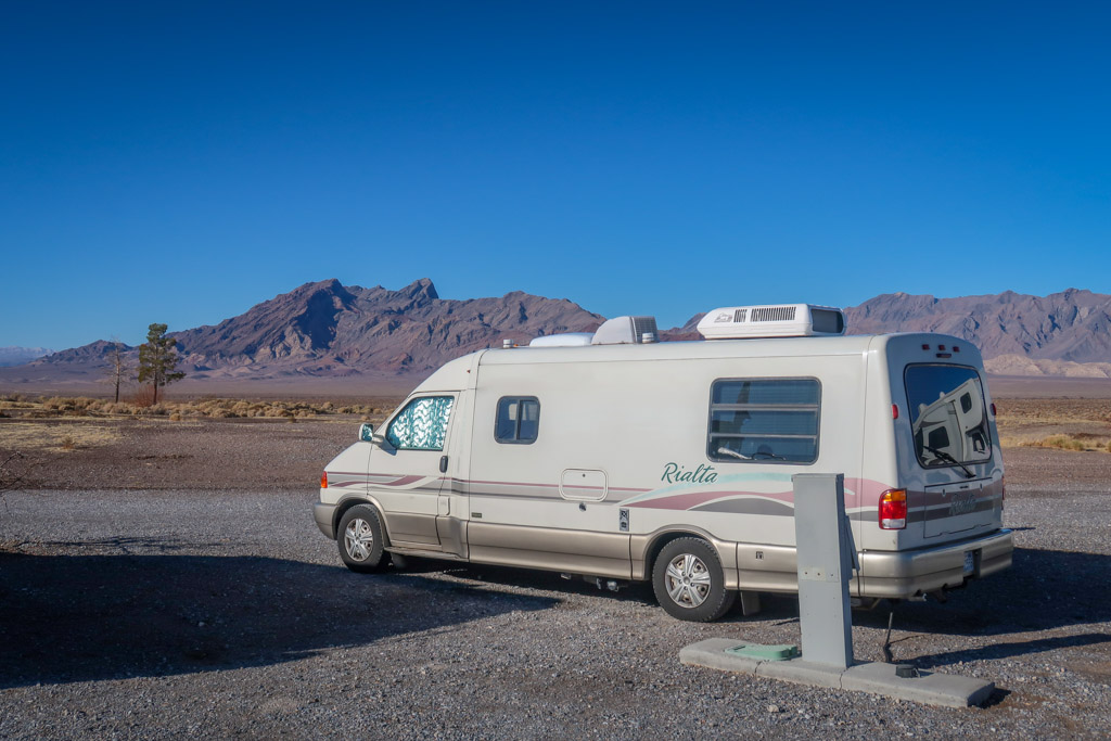 Our Rialta motorhome is parked in a RV resort parking lot with views of the desert mountains in the distance