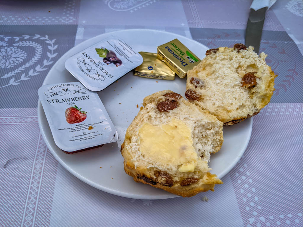 A currant scone spread with butter with jam packets on the side