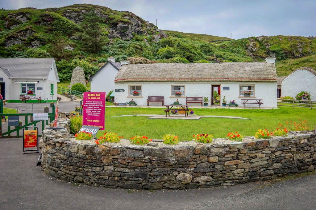 A small village of several cottages with thatched roofs. A sign out front advertises the tea room cafe with a menu.