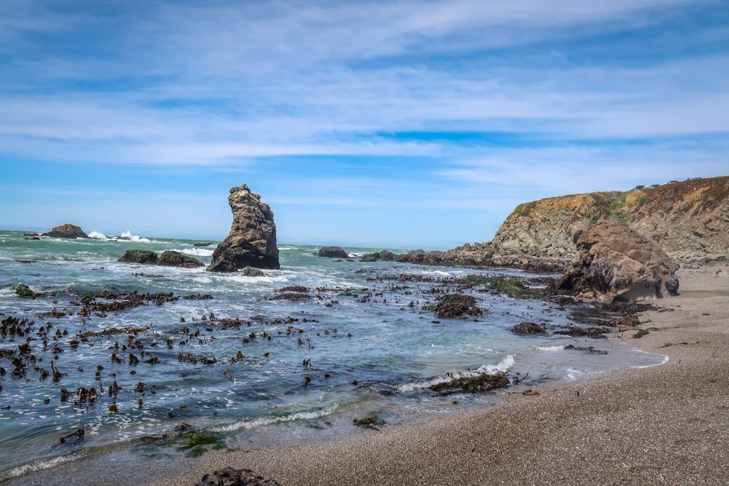 A sandy beach interspersed with rugged rocks and a sea stack poking out of the water