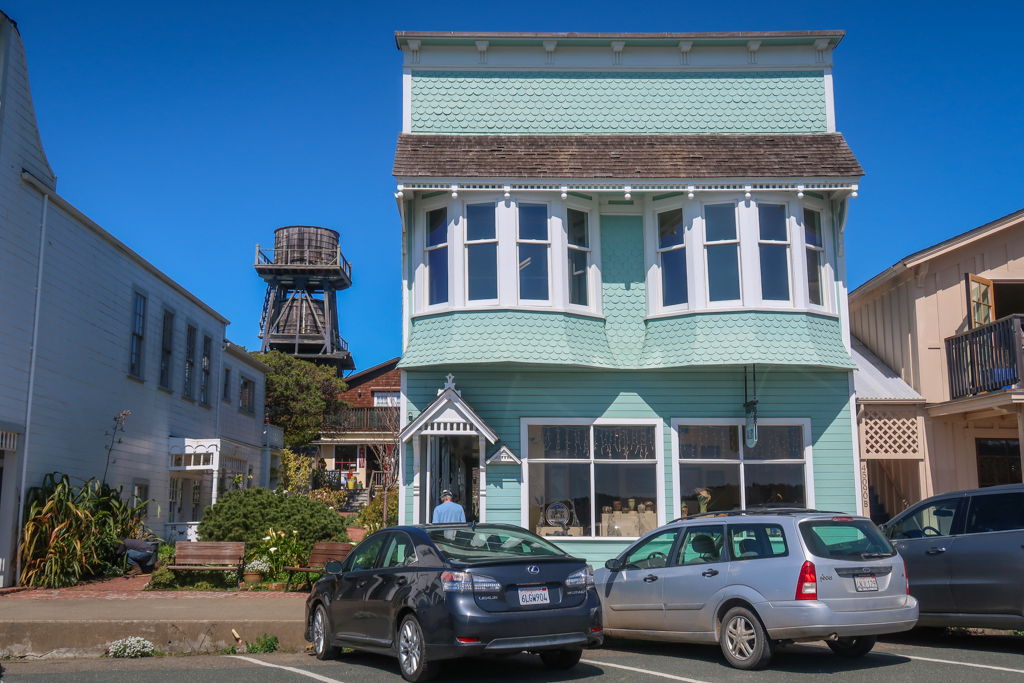 A historic building along Mendocino's Main Street with a wooden water tower in the backgound