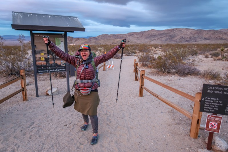 The author poses triumphantly at the North Entrance trailhead with both her hiking poles raised in the air.