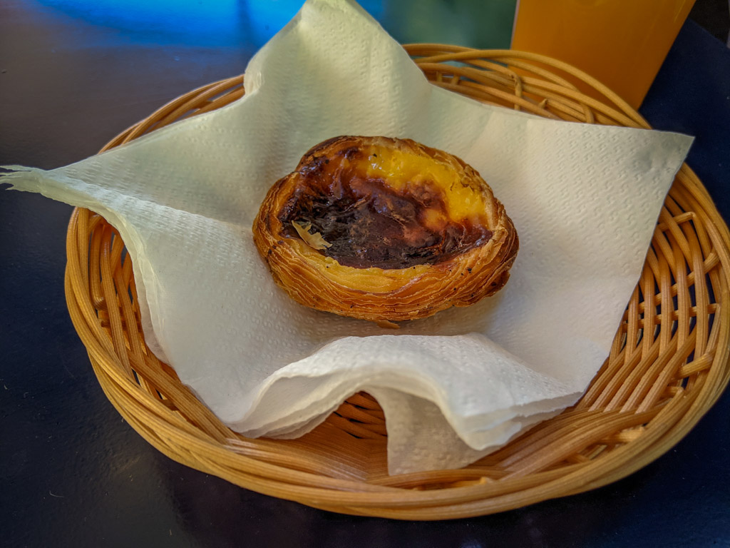 A small custard tart in a flaky pastry shell sits in a display basket