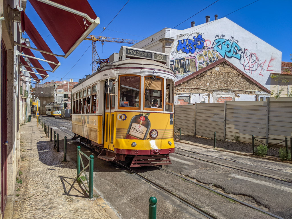 A bright yellow trolley glides down a narrow street with cobblestones and graffiti in the Alfama neighborhood