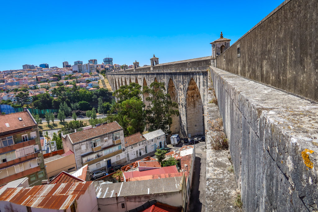 Tue Águas Livres Aqueduct stretches across a valley featuring delicate Roman-style arches