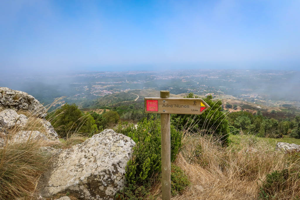 """A hiking signpost stands on an overlook. The marker reads """"PR10. Andre Nunes 1,8 km"""""""