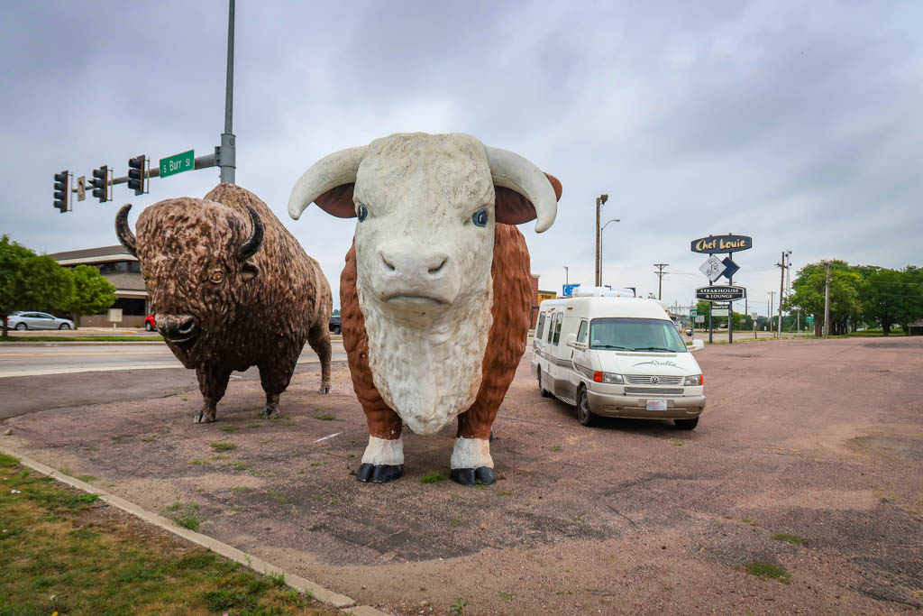 Winnebago Rialta parked next to the Big Steer and Bison Statues. The motorhome is parked next to the statues like it is planning to join them.