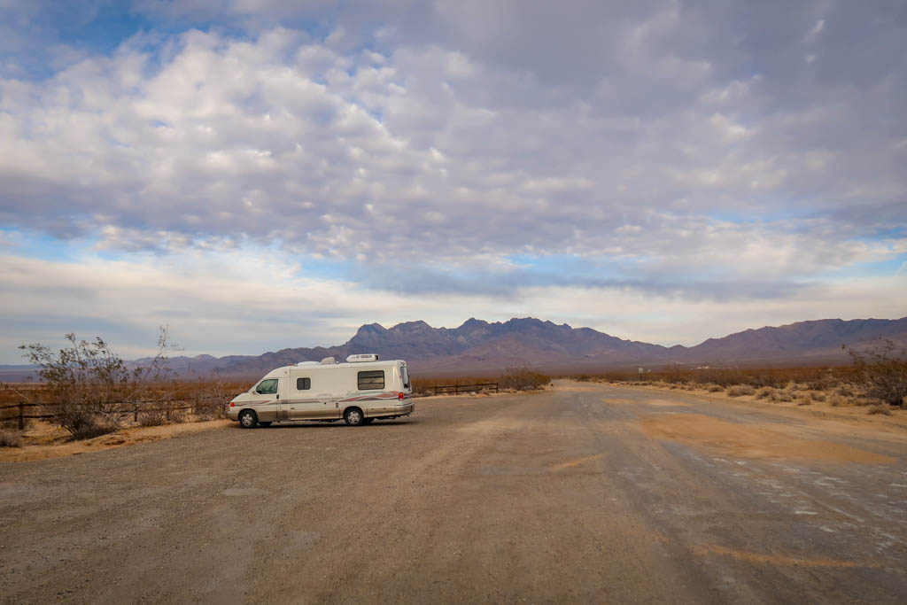 Winnebago Rialta parked near the trailhead for Kelso Dunes with colorful mountains in the distance at Mojave National Preserve