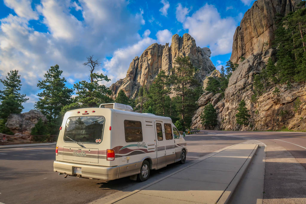 Winnebago Rialta parked in front of Mount Rushmore as viewed from South Dakota Highway 244. Only a portion of Washington's head is visible from this angle.