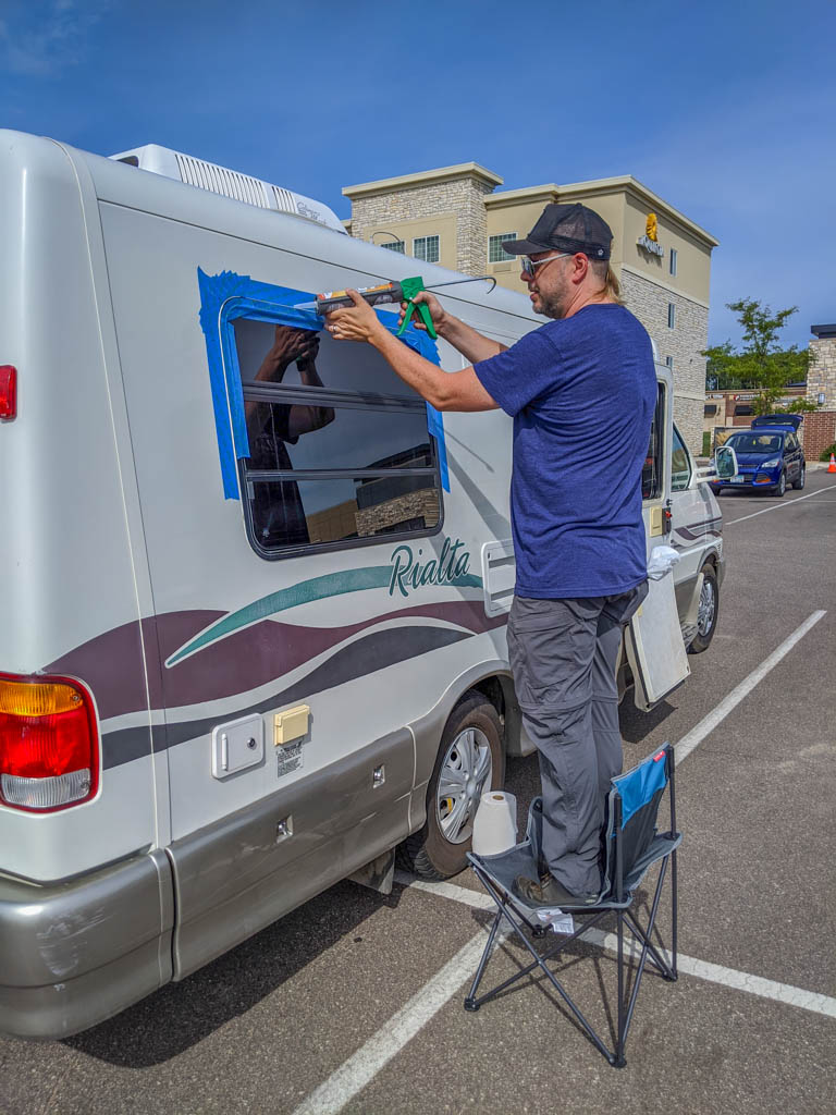 Daniel stands on a chair in a hotel parking lot to caulk around the windows to prevent leaks