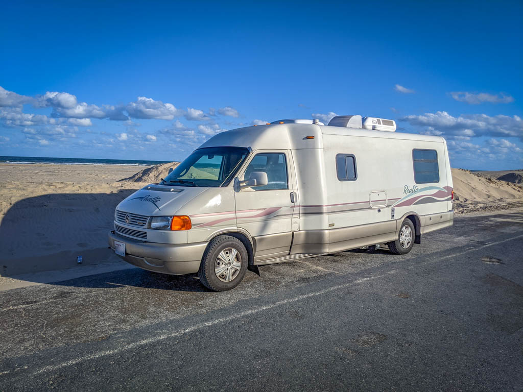 Winnebago Rialta parked along a sandy beach with dunes framing the road on either side in South Padre Island