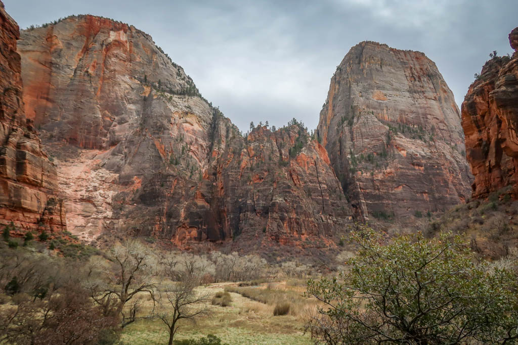 A tall mesa stands alone along the Zion Canyon walls, mostly composed of whitish-colored sandstone