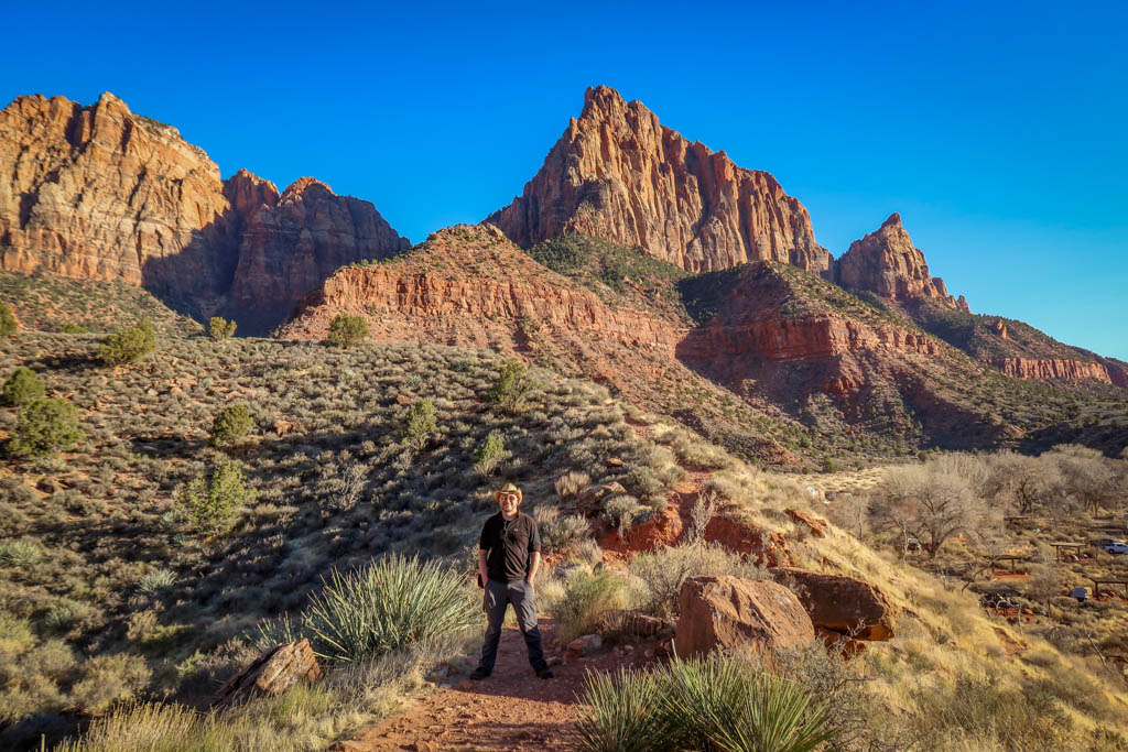 Daniel stands on a hiking path with the tall jagged red walls of Zion Canyon framed behind him.