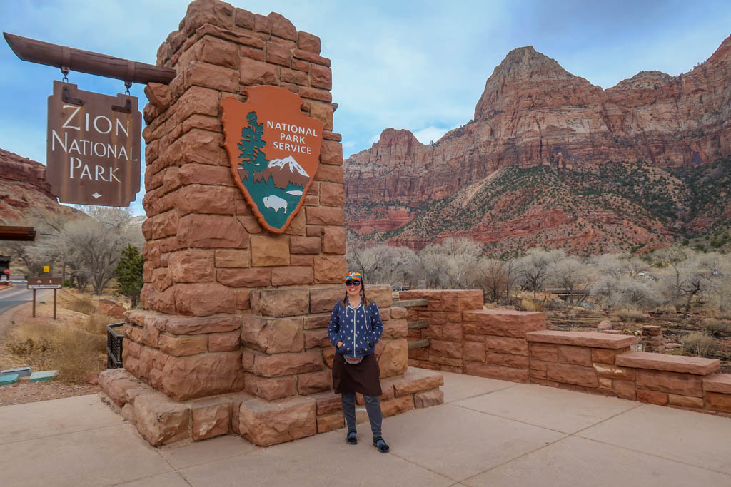 The author stands next to the Zion National Park entrance sign