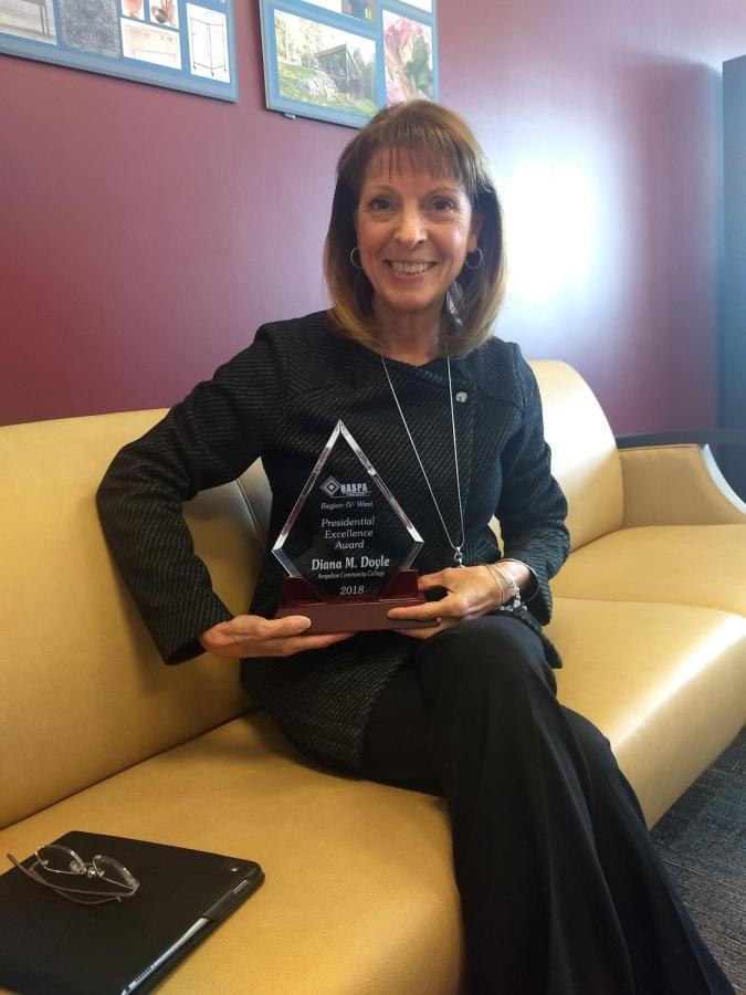 A+cheerful+Dr.+Doyle+showcases+her+Presidential+Excellence+Award.+