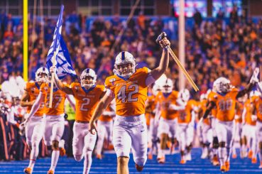 Photo of Boise State football team being led onto the blue field before their game against Hawaii in 2019
