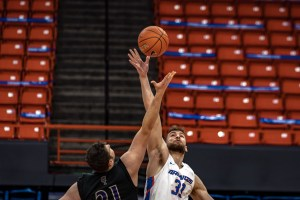 A Boise State basketball player reaches for the ball as an opponent tries to grab the ball.
