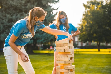 Students playing a very large game of Jenga on a field on Boise State campus.