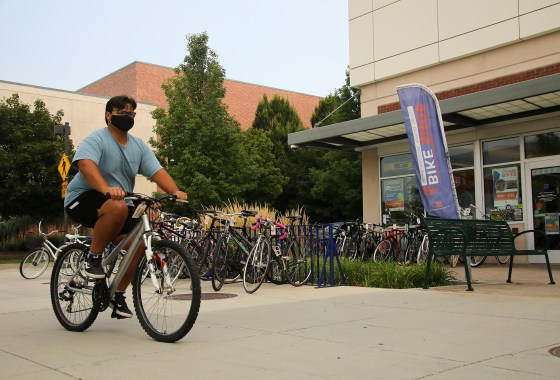 Student riding a bike in front The Cycle Learning Center on Boise State campus.
