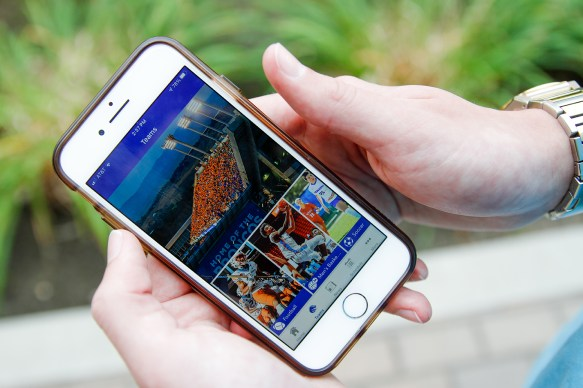 Person holding a phone with the Boise State Broncos Athletics app on the screen