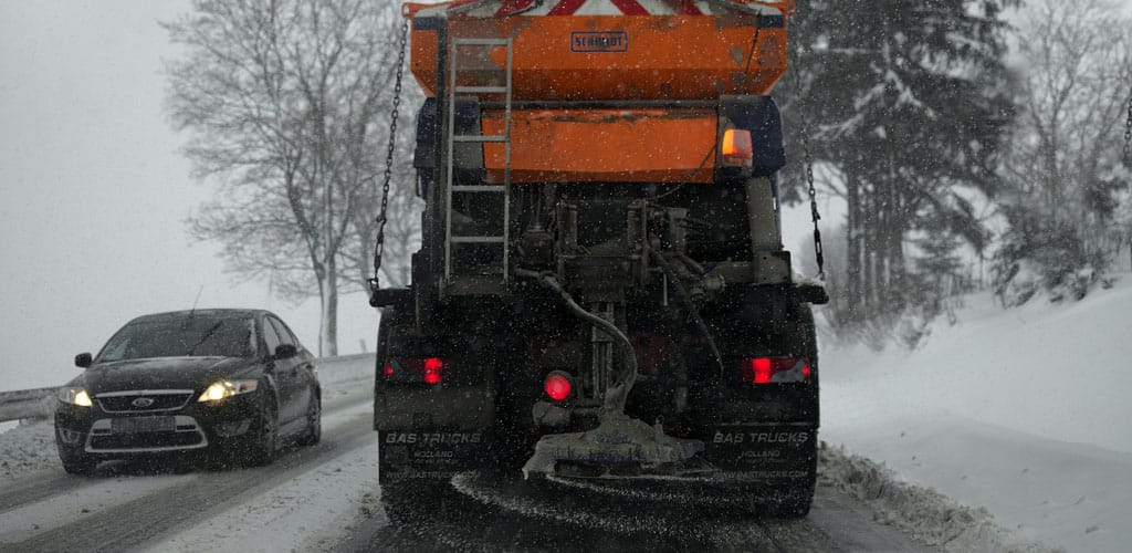 A snowplow applies road salt to a snowy road
