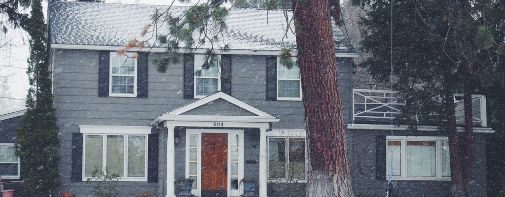 A house in Ohio with a large tree in the front yard and a light dusting of snow
