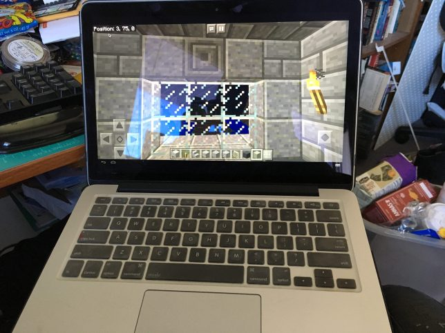 An open Mac laptop displays the game Minecraft on the screen.