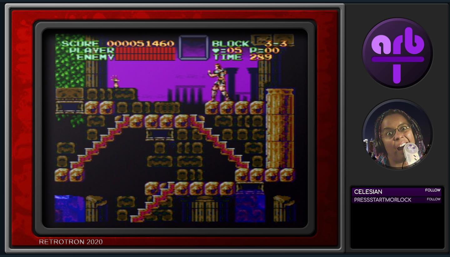A screen laid out to look like an old fashioned TV, with the game Castlevania VI playing in the main part. In a round window onthe right, a black woman with colorful braids gnaws on a SNES controller in frustration