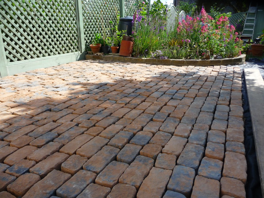 Antique feel cobblestone setts are used to complete this rear garden makeover in a traditional style