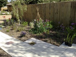 Block paving pathway with soft planting border to rejuvenate a rear garden with a riot of colour